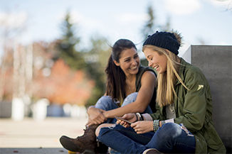 Two college age girl friends are sitting outside on a beautiful fall day. They are talking together before class.